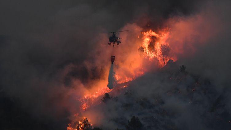 Un hélicoptère lutte contre les flammes à Vitrolles (Bouches-du-Rhône), le 10 août 2016. (BORIS HORVAT / AFP)