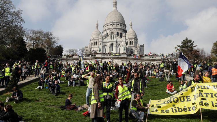 """Des """"gilets jaunes"""" devant la basilique du Sacré Coeur à Paris, le 23 mars 2019. (GEOFFROY VAN DER HASSELT / AFP)"""