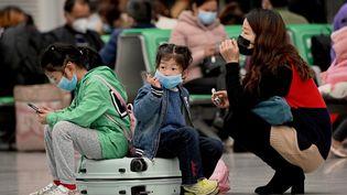 Des voyageurs portent des masques, le 10 mars 2020, à la gare de Changsha, dans le centre de la Chine. (NOEL CELIS / AFP)