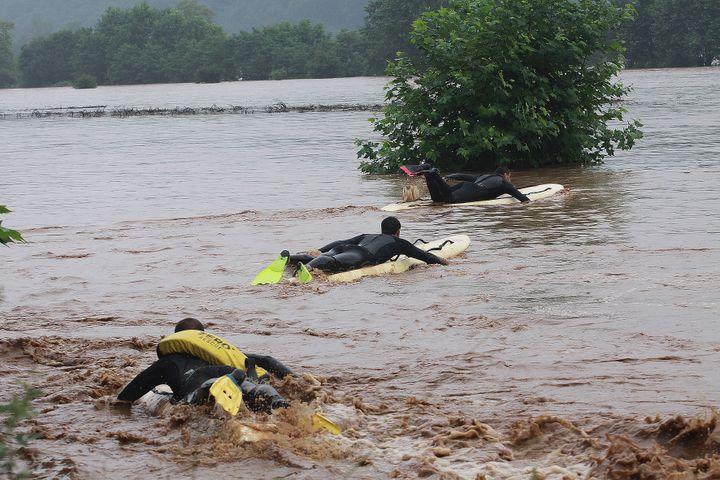 Des secouristes se servent de leur planche de surf pour aller chercher des personnes victimes des inondations à Cambo-les-Bains (Pyrénées-Atlantiques), le 4 juillet 2014. (DANIEL VELEZ / AFP)