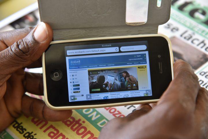 Un homme consulte son compte bancaire à partir de son smartphone le 24 avril 2015 à Abidjan (Côte d'Ivoire) (SIA KAMBOU / AFP)