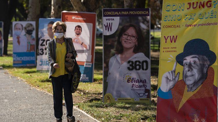 Une femme passe devant des affiches pour l'élection des membres de l'Assemblée constituante, à Santiago le 12 mai 2021. (MARTIN BERNETTI / AFP)
