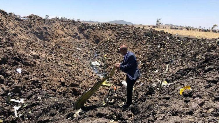Un homme inspecte un débri de l'avion de la compagnie Ethiopian Airlines, qui s'est écrasé près de Bishoftu (Ethiopie), le 10 mars 2019. (XINHUA / ETHIOPIAN AIRLINES)