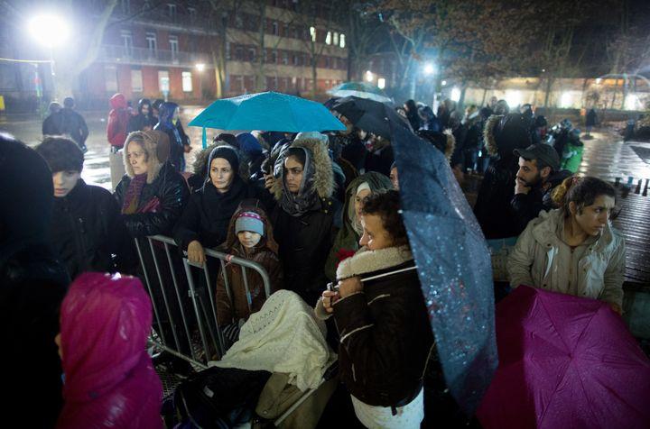 Des demandeurs d'asile se pressent aux portes du ministère de la Santé et des Affaires sociales de Berlin, le 21 décembre 2015. (KAY NIETFELD / DPA)