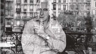 Le réalisateur Claude Sautet chez lui à Paris se reflète dans la fenêtre de son appartement, avenue des Gobelins. (PARIGRAMME / Coll Yves Sautet/DR)