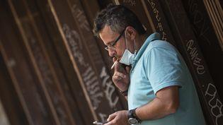 Un homme fume une cigarette dans une rue de Valence, le 13 août 2020, en Espagne. (JOSE JORDAN / AFP)