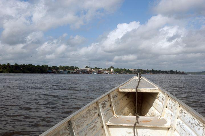 Une pirogue navigue sur le fleuve Oyapock, frontière naturelle entre la Guyane et le Brésil, le 27 juillet 2012 près de Saint Georges de l'Oyapock (Guyane). (JEROME VALLETTE / AFP)