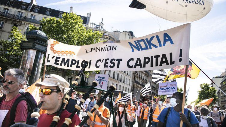 Des salariés de l'équimentier télécom Nokia défilent à Paris mercredi 8 juillet pour protester contre un plan de départs volontaires. (YANN CASTANIER / HANS LUCAS)