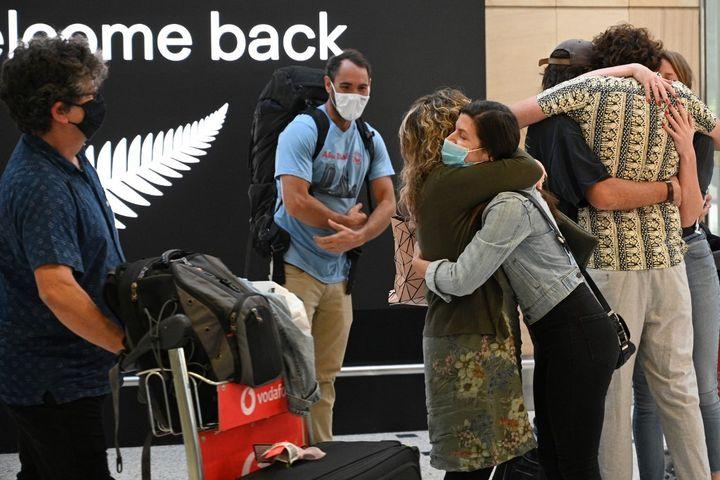 Des familles se retrouvent à l'aéroport de Sydney, en Australie, le 19 avril 2021. (SAEED KHAN / AFP)