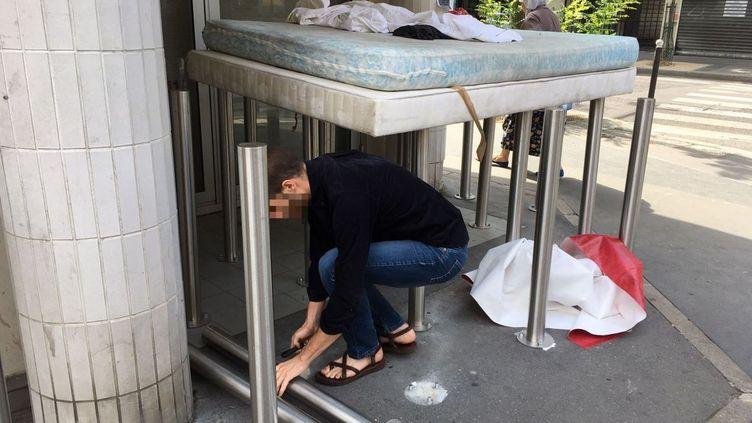 Un homme dévisse les poteaux anti-SDF devant une agence de la Caisse d'épargneà Paris (14e arrondissement), le 28 juillet 2019. (FREDERIQUE HOVASSE / FRANCE 3 ILE DE FRANCE)
