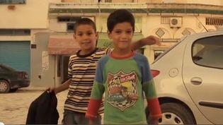 """Capture d'écran montrant deux enfants du quartier de l'Ariana, banlieue de Tunis (Tunisie) figurant dans le clip """"""""Houmani"""" des rappeurs Hamzaoui Med Amine et Kafon. (YOUTUBE / FRANCETV INFO)"""