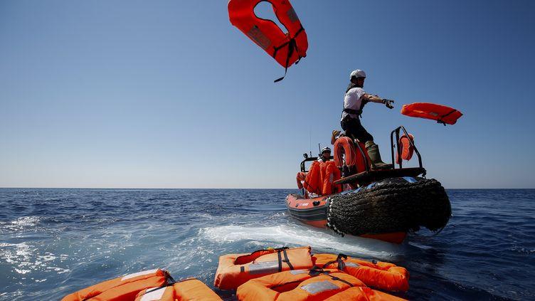 Des membres de l'ONG SOS Méditerranée et Médecins Sans Frontières (MSF) réalisent un exercice de sauvetage près du navire de sauvetage Aquarius, en pleine mer entre Lampedusa et la Tunisie, le 23 juin 2018 . (PAU BARRENA / AFP)