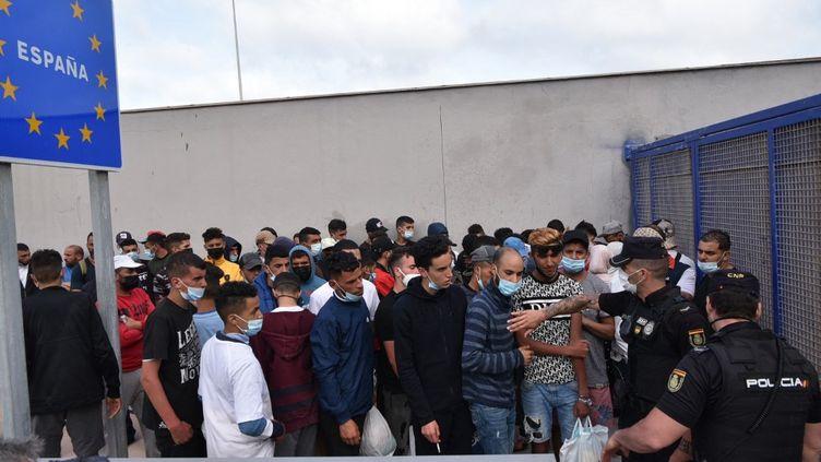 Des migrants attendent de traverser la frontière vers le Maroc dans l'enclave espagnole de Ceuta, le 20 mai 2021. (ANTONIO SEMPERE / AFP)