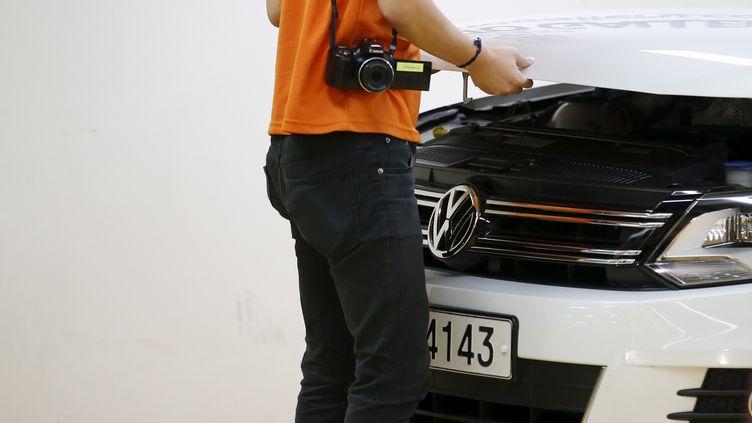 Un homme soulève le capot d'une Volkswagen, le 2 octobre 2015, à Séoul (Corée du Sud). (KIM HONG-JI / REUTERS)