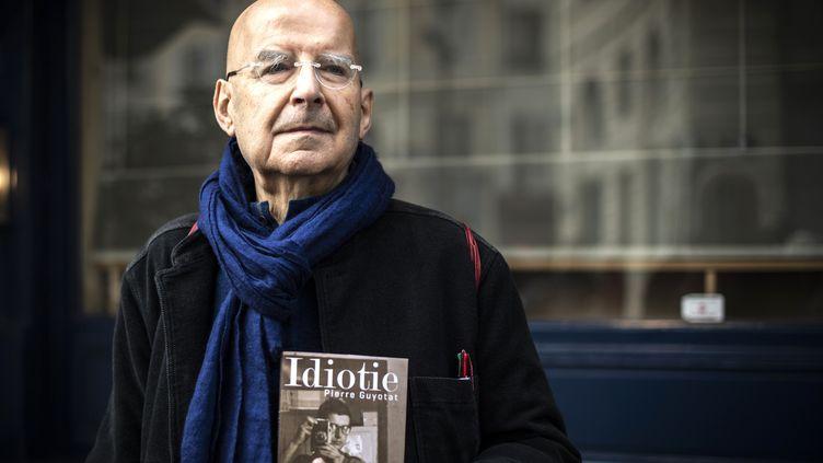 """L'écrivain Pierre Guyotat pose avec son livre """"Idiotie"""", lauréat du prix Medicis en 2018, le 6 novembre 2018. (PHILIPPE LOPEZ / AFP)"""