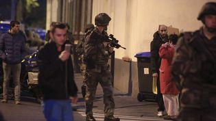 Un militaire patrouillant à Saint-Denis (Seine-Saint-Denis), au milieu de la population, alors qu'une opération anti-terroriste est en cours, mercredi 18 novembre. (THIBAULT CAMUS / AP / SIPA)