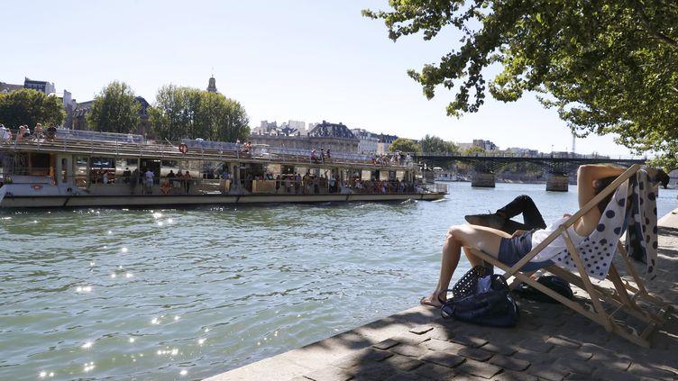 Des personnes sont installées sur les rives de la Seine, à Paris, durant une alerte canicule, le 24 août 2016. (PATRICK KOVARIK / AFP)