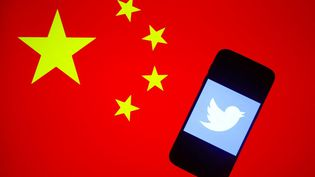 Le logo de Twitter représenté dans l'écran d'un smartphone avec le drapeau chinois en arrière-plan (illustration). (BEATA ZAWRZEL / NURPHOTO)