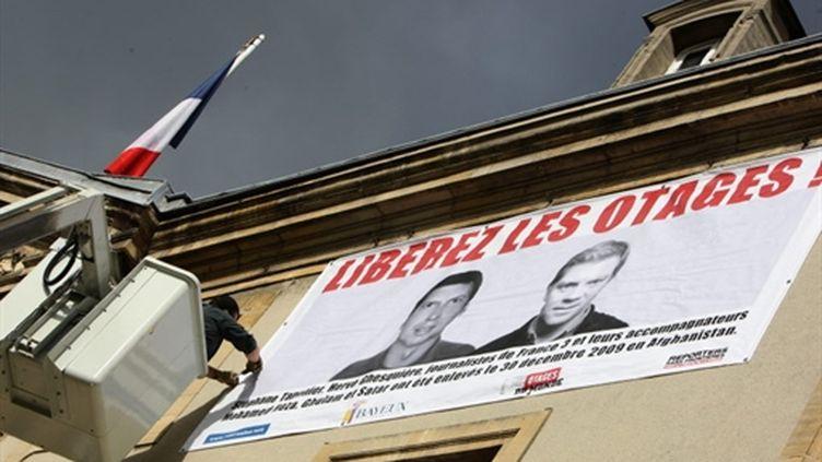 Une banderole demandant la libération d'Hervé Ghesquière et Stéphane Taponier à la mairie de Caen (7 juin 2010) (AFP/KENZO TRIBOUILLARD)
