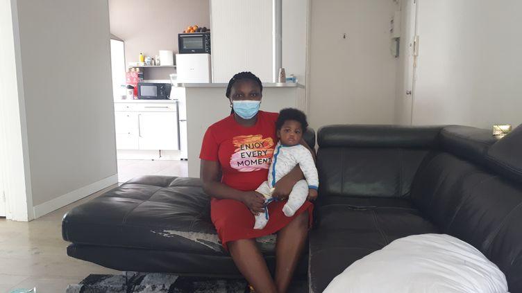 Jupsy et son fils, Preston, âgé de 7mois, dans le salon de leur appartement de Melun, qu'ils occupent depuis 8 mois, le 31 mai 2021. (THEO BOSCHER / RADIO FRANCE)