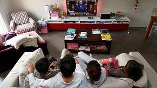 Une famille parisienne regarde le Premier ministre français, Edouard Philippe, s'exprimer à l'Assemblée nationale, le 28 avril (photo d'illustration). (DAMIEN MEYER / AFP)