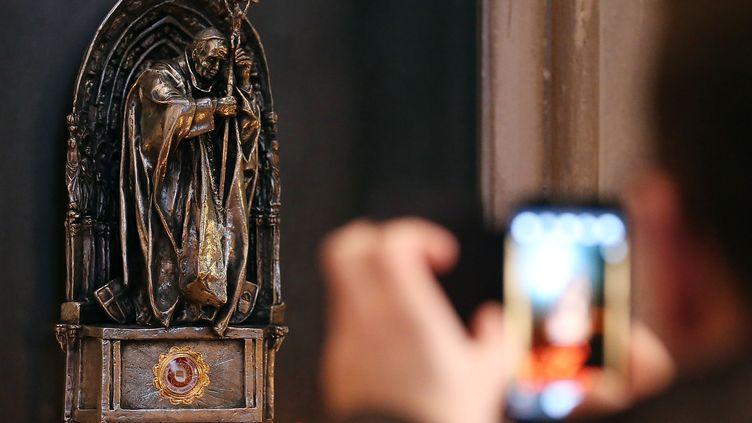 Un touriste photographie la statue du pape Jean Paul II qui contient une relique du souverain pontife, à Cologne (Allemagne), le 10 décembre 2013. (OLIVER BERG / DPA / AFP)