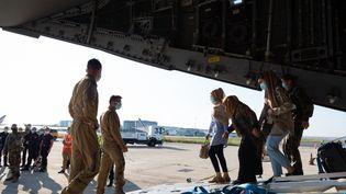 Des militaires français aident des évacués à débarquer d'un avion en provenance de Kaboul, à Abou Dhabi (Emirats Arabes Unis), le 26 août 2021. (EYEPRESS NEWS / AFP)
