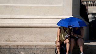 Des personnes s'abritent sous l'ombre d'un parapluie lors de l'épisode de chaleur à Paris, le 26 juin 2019. (KENZO TRIBOUILLARD / AFP)