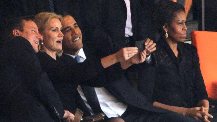 Le Premier ministre britannique David Cameron, son homologue danoiseHelle Thorning Schmidt et le président américain Barack Obama se prennent en photo, le 10 décembre 2013, lors de la cérémonie d'hommage à Nelson Mandela au stade Soccer City deJohannesburg (Afrique du Sud). (ROBERTO SCHMIDT / AFP)