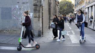 Des utilisatrices de trottinettes électriques, à Paris, le 22 octobre 2018. (ONLY FRANCE / AFP)