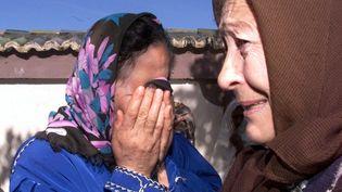 Des voisins pleurent dans le village de Tipaza, à quelque 70 kilomètres au sud-ouest d'Alger, le 13 mars 2001, après un massacre. (HZ / AFP)