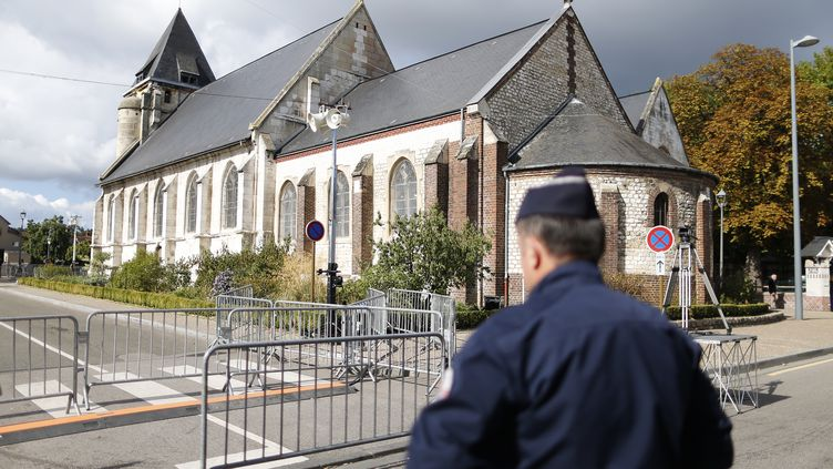 Un officier de police devant l'église de Saint-Etienne-du-Rouvray (Seine-Maritime) lors de sa réouverture, le 2 octobre 2016. (CHARLY TRIBALLEAU / AFP)
