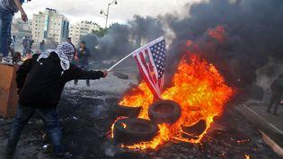 Un Palestinien brûle un drapeau américain le 7 décembre 2017 près de Ramallah, en Cisjordanie. (ABBAS MOMANI / AFP)
