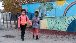 Deux fillettes de 7 ans et 9 ans portent un masqueà l'école de Grézieu-la-Varenne (Rhône), le 2 novembre 2020. (SEBASTIEN RIEUSSEC / HANS LUCAS / AFP)