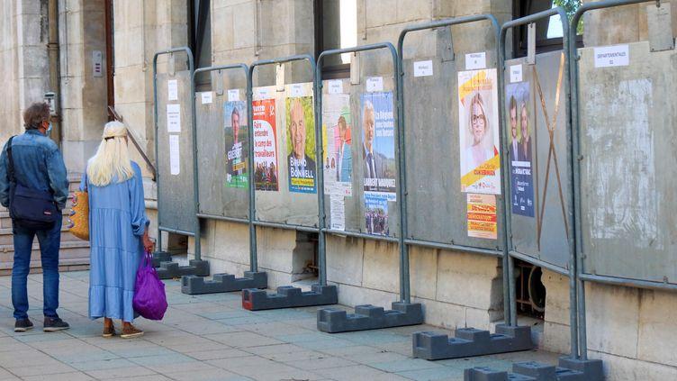 Des passants s'arrêtent devant les affiches des candidats aux élections dans la région Auvergne-Rhône-Alpes, le 31 mai 2021, à Valence (Drôme). (NICOLAS GUYONNET / HANS LUCAS / AFP)