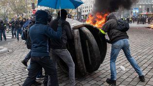 """Des manifestants préparent une barricade dans les rues de Paris, le 16 novembre 2019, lors de la manifestation des """"gilets jaunes"""". (JEROME GILLES / NURPHOTO / AFP)"""