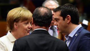 La chancelière allemande, Angela Merkel, discute avec le Premier ministre grec, Alexis Tsipras, sous les yeux deFrançois Hollande (de dos), le 12 juillet 2015 à Bruxelles (Belgique). (JOHN MACDOUGALL / AFP)