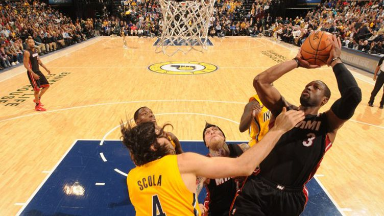 Dwyane Wade (Miami) en difficulté face à la défense de Luis Scola (Indiana) (RON HOSKINS / NBAE / GETTY IMAGES)