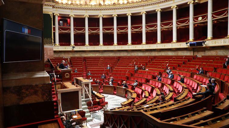Des députés votent à mains levées le projet de loi d'urgence sanitaire, le 22 mars 2020, à l'Assemblée nationale, à Paris. (LUDOVIC MARIN / AFP)