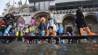 A Venise (Italie), les touristes sont en bottes et sur des passerelles sur laplace Saint-Marc inondée, le 7 novembre 2014 (OLIVIER MORIN / AFP)