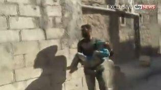 Capture d'écran montrant la petite Syrienne dans les bras de son sauveteur, à Alep, le 23 septembre 2016. (SKY NEWS / APTN)