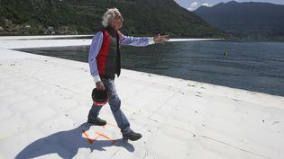 """Christo Vladimirov Javacheff marche sur son oeuvre """"LesFloating Piers"""" sur le lac d'Iseo (Italie), le 7 juin 2016. (LUCA BRUNO / AP / SIPA)"""
