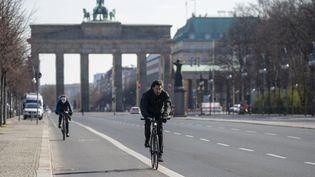 Des cyclistes devant la porte de Brandebourg à Berlin (Allemagne). Photo d'illustration. (ODD ANDERSEN / AFP)