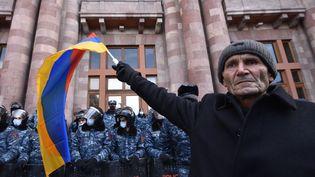 Un homme agite un drapeau arménien devant les forces de l'ordre lors d'un rassemblement pour demander la démission du Premier ministre Nikol Pashinyan, à Erevan le 24 décembre. (KAREN MINASYAN / AFP)