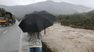 Une femme fait face à une rivière en crue à Ponte-Leccia (Haute-Corse), lors d'un épisode d'intempéries le 24 novembre 2016. (PASCAL POCHARD-CASABIANCA / AFP)