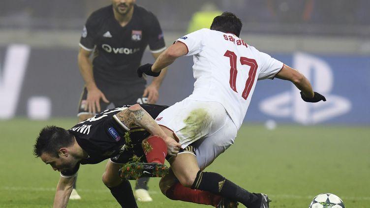 Mathieu Valbuena au sol face au défenseur de Seville dans une lutte farouche