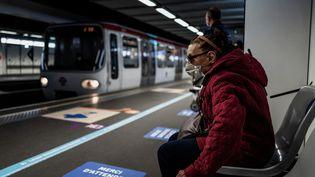 Une femme patiente dans une station de métro à Lyon, lundi 11 mai 2020. (JEFF PACHOUD / AFP)