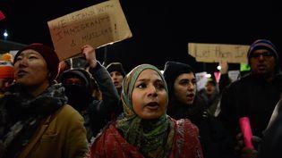 Des manifestants protestent contrela décision du président américain Donald Trump d'interdire l'arrivée de ressortissants de sept pays, à l'aéroportJohn F. Kennedy de New York (Etats-Unis), le 28 janvier 2017. (STEPHANIE KEITH / GETTY IMAGES NORTH AMERICA / AFP)