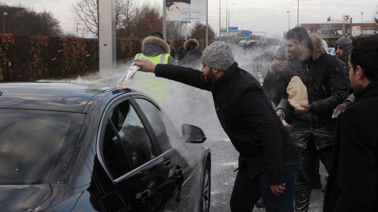 Des chauffeurs de VTC lancent de la farine sur un véhicule, près de l'aéroport RoissyCharles-de-Gaulle, le 16 décembre 2016. (GEOFFROY VAN DER HASSELT / AFP)