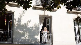Une femme âgée munie d'un masque de protection nettoie son balcon, en pleine épidémie de Covid-19, le 11 avril 2020 à Nantes(Loire-Atlantique). (J?R?MIE LUSSEAU / HANS LUCAS / AFP)
